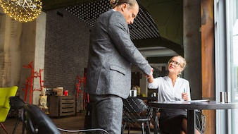 Two businesspeople shaking hands in restaurant