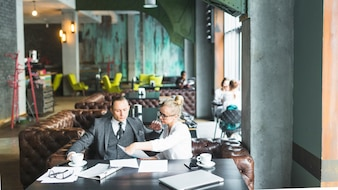 Two businesspeople sitting together checking document in caf�