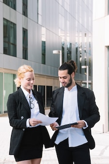 Two businesspeople standing outside the office building checking paper document