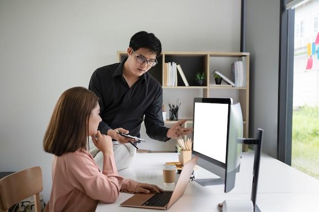 두 사업가가 현대 사무실에서 프로젝트 전략을 이야기하고 있습니다.