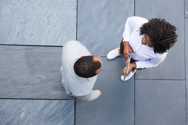 Two businesspeople talking while standing on paving slab