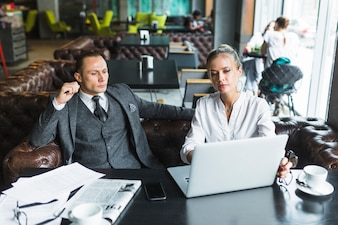 Two businesspeople using laptop in restaurant