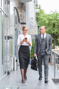 Two businesspeople walking together outside office