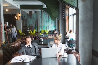 Two businesspeople with laptop sitting in restaurant