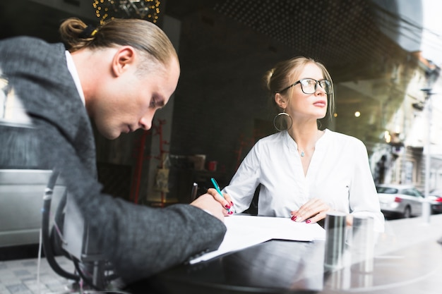 Two businesspeople working on document in restaurant