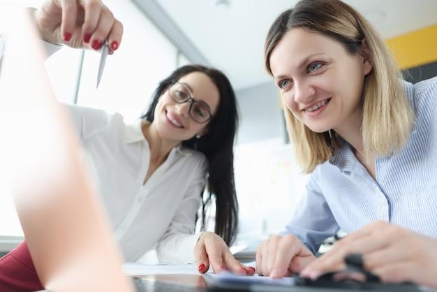 두 사업가 랩톱에서 시연하여 비즈니스 프로세스를 논의하고 있습니다.