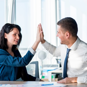 Two businesswoman and businessman giving hi-five across the table