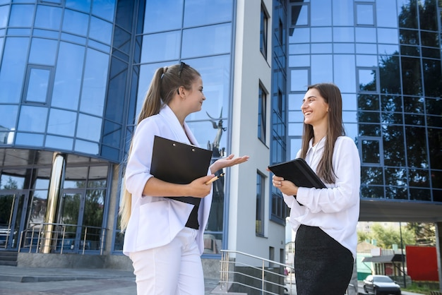 Две бизнес-леди держат планшеты и разговаривают напротив офисного здания