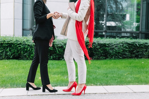 Two businesswoman wearing high heels shaking hands