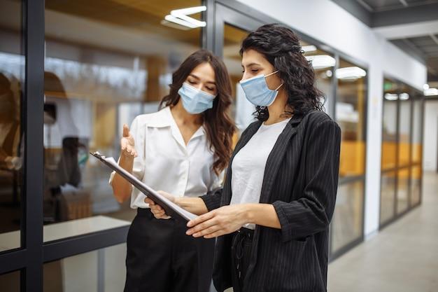 2人のビジネスウーマンが、医療用滅菌マスクを着用してオフィスでの作業について話し合っています。コロナウイルスのパンデミック検疫中に働いています。