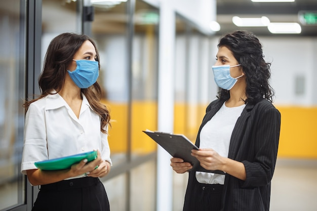 Two businesswomen discuss working matters at the office wearing medical sterile masks. new normal, health care and safety measures concept.