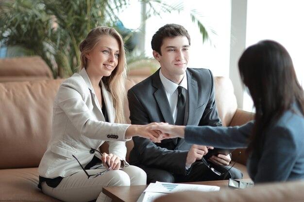 Две бизнес-леди держат друг друга за руки, сидя за столом