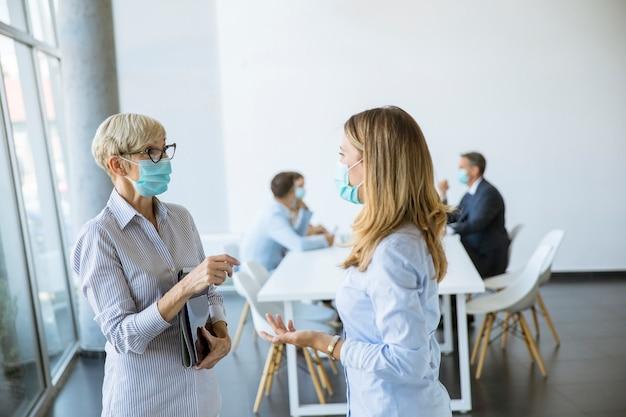 Две деловые женщины, зрелая и молодая, разговаривают в офисе и носят маску в качестве защиты от вирусов