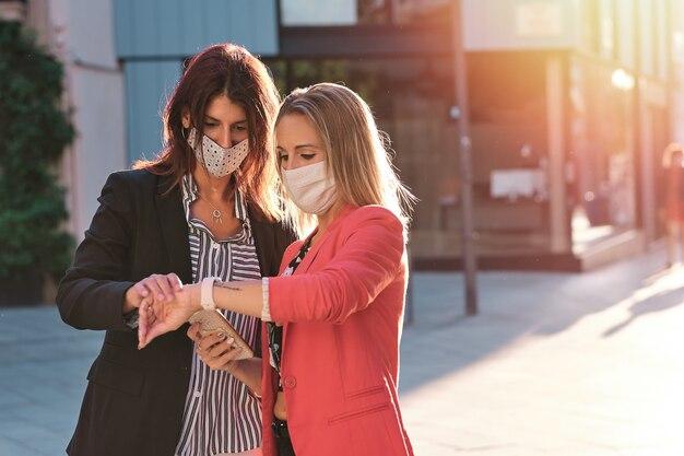 Две женщины-предприниматели на открытом воздухе с помощью мобильных телефонов и маски