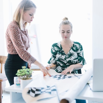 Two businesswomen preparing checkered flag on chart in office