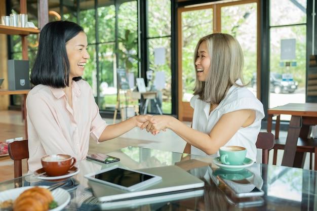 地元のコーヒーショップで握手する2人のビジネスウーマン。コーヒーを飲みながらカフェでビジネスプロジェクトについて話し合う2人の女性。スタートアップ、アイデア、ブレインストーミングのコンセプト。カフェでノートパソコンを使用しています。