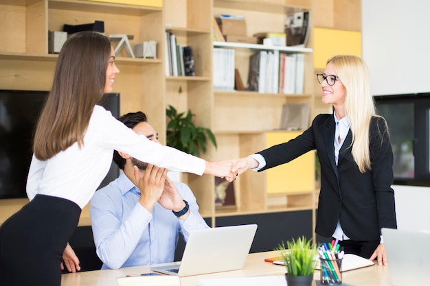 Two businesswomen shaking hands over a desk as they close a deal or partnership