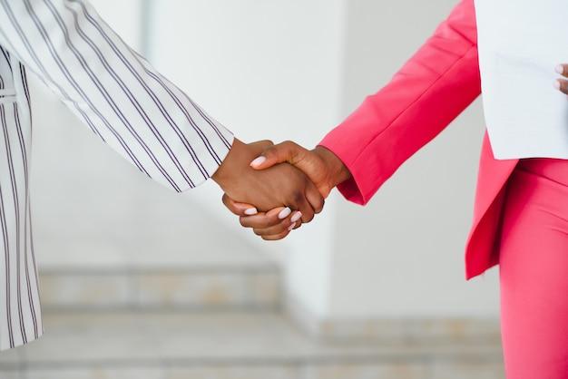 現代のオフィスのロビーで握手する2人のビジネスウーマン