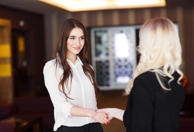 現代のオフィスで握手する2人のビジネスウーマン