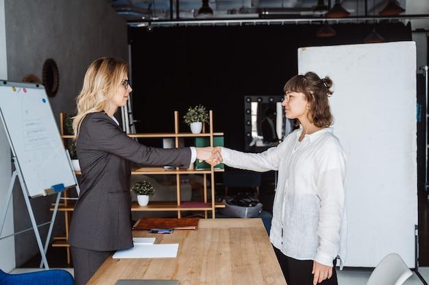 オフィスで握手する2人のビジネスウーマン