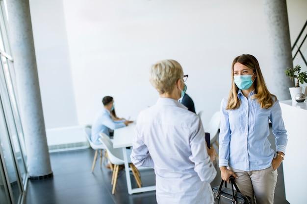 2人のビジネスウーマンがオフィスで話し、ウイルス保護としてマスクを着用