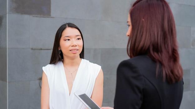 ワークスペースで話している2人のビジネスウーマンタブレットを持った女性の上司アジア人労働者