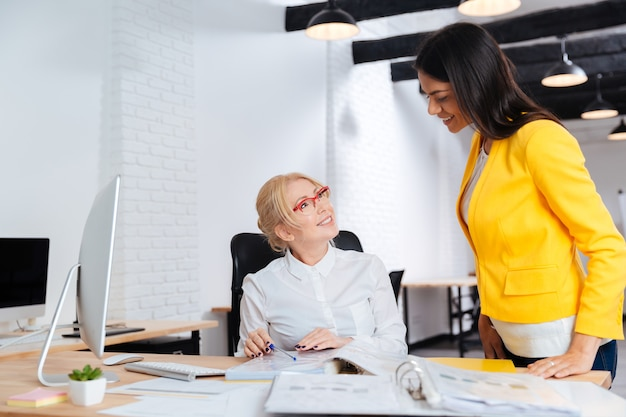 Two businesswomen talking and smiling while reviewing a work plan