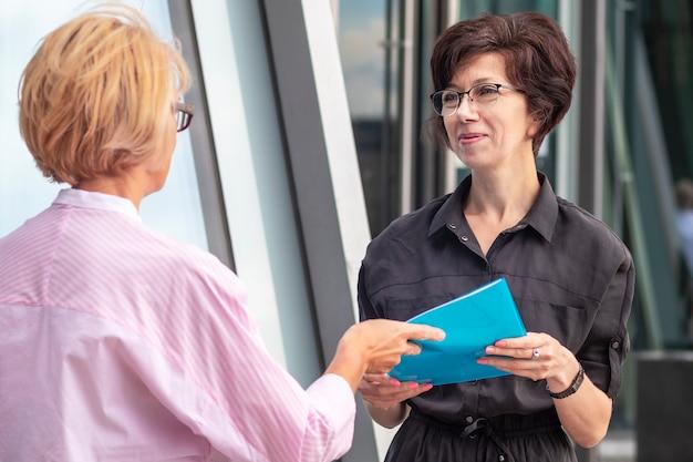 Две бизнес-леди с документами на открытом воздухе