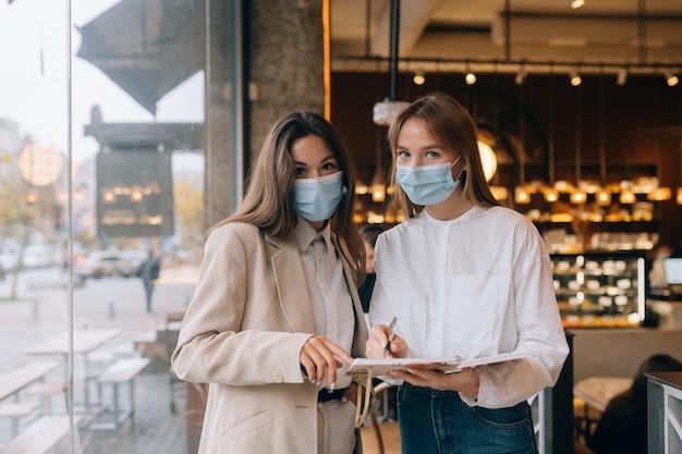 仕事についての異なる見解を議論しているフェイスマスクを持つ2人のビジネスウーマン