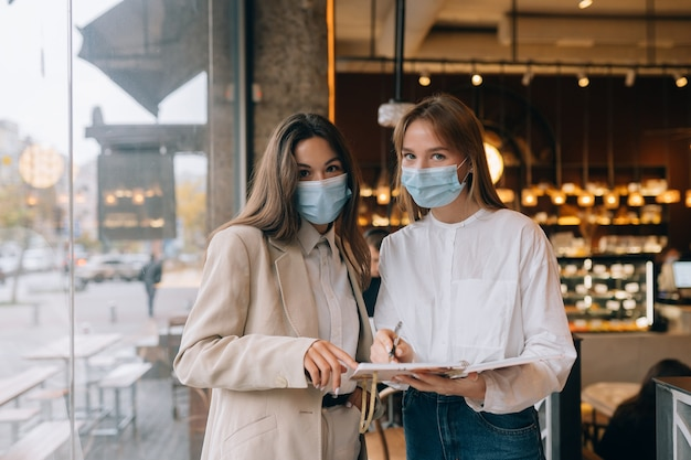 Two businesswomen with their face masks debating different views on work