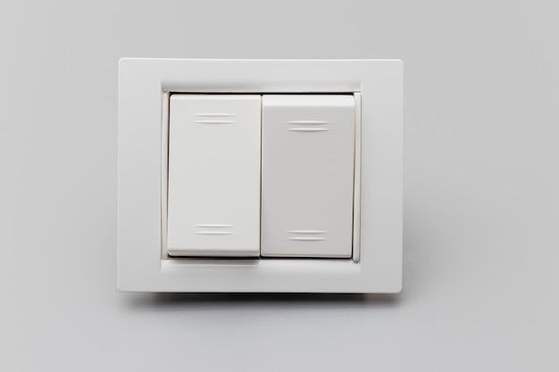 灰色の背景にある2ボタンの白いスイッチ。修理のための家の電気技師。省エネコンセプト。閉じる。フルフォーカス。コピースペース。