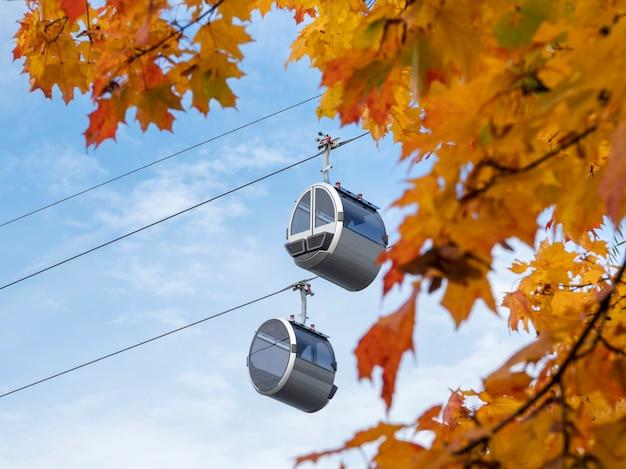 青い秋の空にあるケーブルカーの2つのキャビン。