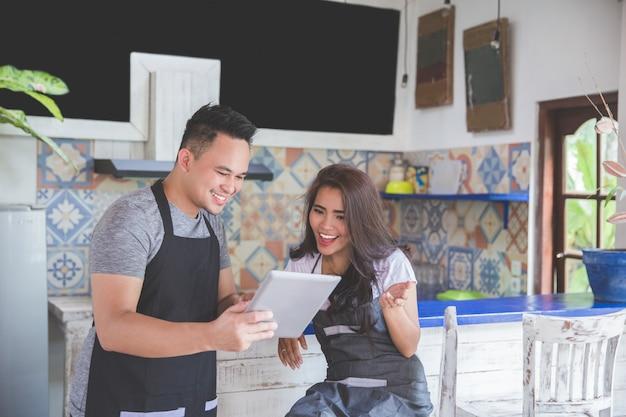 Два кафе работник с помощью планшета