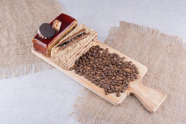 木の板に2つのケーキとコーヒー豆。