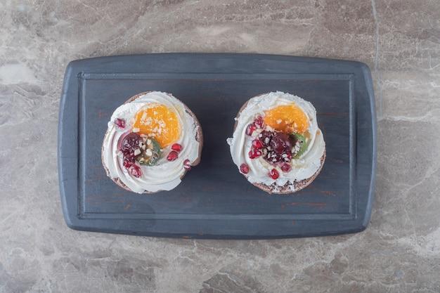 大理石の表面の海軍ボード上の2つのケーキ