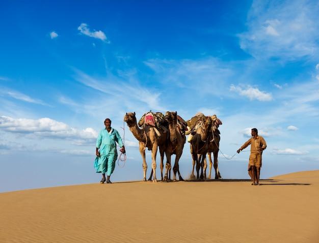 タール砂漠の砂丘でのラクダと2つのラクダ(ラクダドライバー)