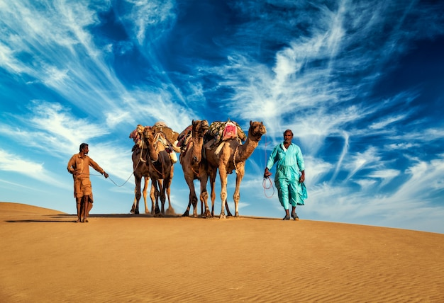 Два погонщика верблюдов с верблюдами в дюнах пустыни тар