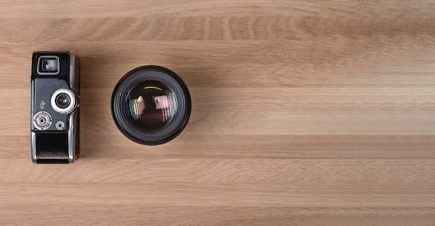 두 세대의 카메라, 빈티지 렌즈와 모던 렌즈. 사진 배너. 나무 배경에 텍스트를위한 공간으로 배너.
