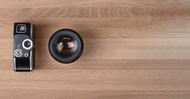 Two camera generations, vintage one and modern lenses. photography banner. banner with room for text on wood background.