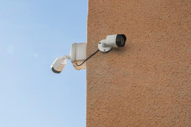 건물 외벽에 설치된 2대의 카메라 감시 또는 실외 보안 시스템. 개념 보안, 원격 감시, 감시.
