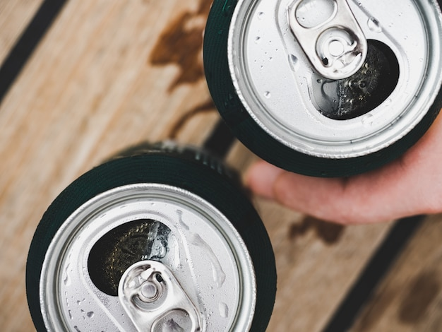 Two can of beer, female and male hands