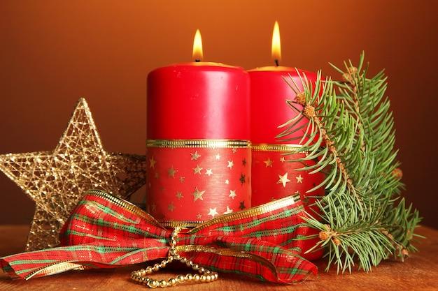 茶色の背景に2つのキャンドルとクリスマスの装飾