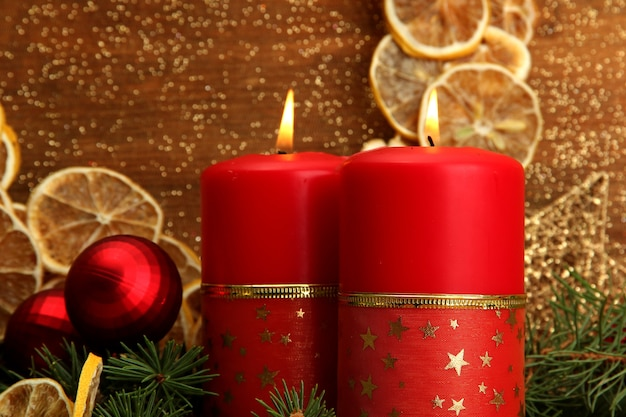金色の背景に2つのキャンドルとクリスマスの飾り