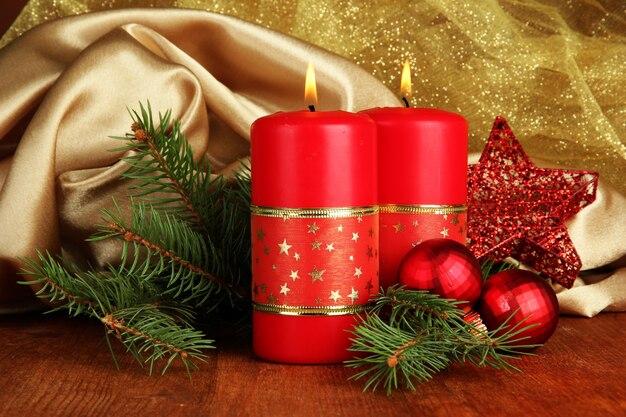 金色の布の背景に2つのキャンドルとクリスマスの装飾