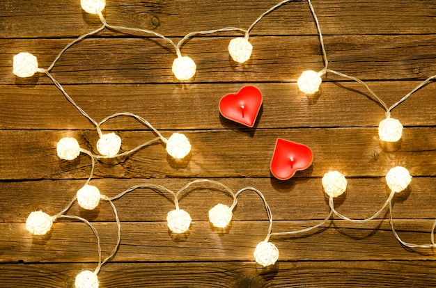 Two candles in the shape of heart among the glowing lanterns made of rattan on a wooden background