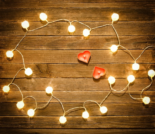 Two candles in the shape of heart among the glowing lanterns made of rattan on a wooden surface. view from above, space for text