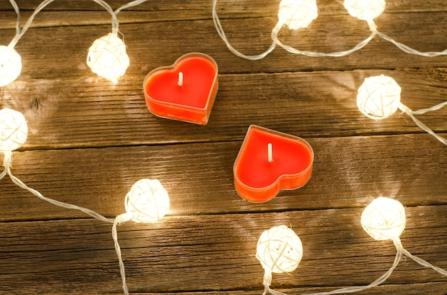 木製の背景に籐で作られた光るランタンの中でハートの形をした 2 つのキャンドル。上から見る