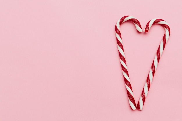 Two candy canes forming a heart shape, on pink background with copy space valentine's day concept.