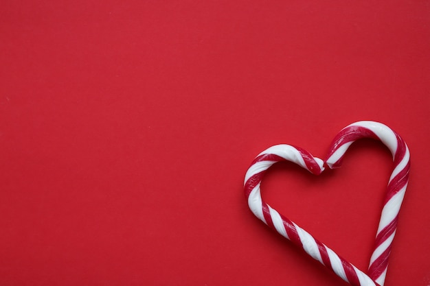 Two candy canes forming a heart shape on red background. love concept.