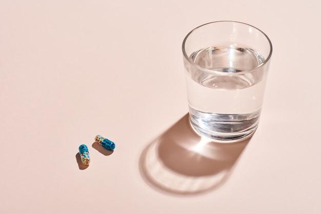2つのカプセルとコップ1杯の水